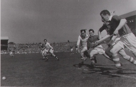 The sky looks turbulent over the 1953 All-Ireland Final. Galway's Miko McInerney tries to get around Cork's Tony O'Shaughness, John Lyons and Gerry O'Riordan, while Vincent Twomey and Hubert Gordon are further out the field.