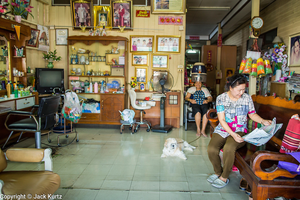 13 JANUARY 2013 - BANGKOK, THAILAND:  A woman reads the newspaper in her living room/beauty parlor while a customer sits under the dryer in the Bang Luang neighborhood of Bangkok. The Bang Luang neighborhood lines Khlong (Canal) Bang Luang in the Thonburi section of Bangkok on the west side of Chao Phraya River. It was established in the late 18th Century by King Taksin the Great after the Burmese sacked the Siamese capital of Ayutthaya. The neighborhood, like most of Thonburi, is relatively undeveloped and still criss crossed by the canals which once made Bangkok famous. It's now a popular day trip from central Bangkok and offers a glimpse into what the city used to be like.     PHOTO BY JACK KURTZ