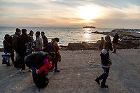 MYTILINI, GREECE - FEBRUARY 09: Refugees stand while waiting for a bus run by UNHCR for being transferred to the Moria refugee camp after their arrival to a beach in Lesvos after crossing the Aegean sea by dinghy on February 09, 2015 in Mytilini, Greece. Hundreds of refugees arrive everyday at the beaches of Lesvos after being smuggled from the Turkish coast where they board unsafe boats to cross the Aegean sea. Photo: © Omar Havana. All Rights Are Reserved