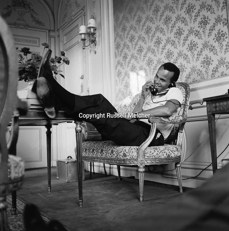 Feet up, relaxing, Harry Belafonte in his suite in the Hotel Raphael in Paris.<br /> <br /> <br /> Detendus, Harry Belafonte dans sa suite à l'Hôtel Raphael à Paris .