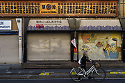 An older Japanese woman pushes a bicycle passed the shutters store fronts of shops in what remains of Tsukiji market. Tsukiji, Tokyo, Japan. Wednesday February 5th 2020