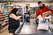 "03 AUGUST 2020 - JEWELL, IOWA:  GARREN ZANKER, manager of the Jewell Market, runs the cash register while a customer pays for her groceries. The only grocery store in Jewell, a small community in central Iowa, closed in 2019. It served four communities within a 20 mile radius of Jewell. Some of the town's residents created a cooperative to reopen the store. They sold shares to the co-op and  held fundraisers through the spring. Organizers raised about $225,000 and bought the store, which had its ""soft opening"" July 8. The store celebrated its official reopening Monday August 3. Before the reopening, Jewell had been a ""food desert"" for seven months. The USDA defines rural food deserts as having at least 500 people in a census tract living 10 miles from a large grocery store or supermarket. There is a convenience store in Jewell, but it sells mostly heavily processed, unhealthy snack foods that are high in fat, sugar, and salt.         PHOTO BY JACK KURTZ"