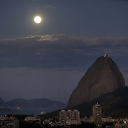 The moon rises above the summit of Sugar Loaf Mountain, one of the iconic locations with breathtaking views of Rio de Janeiro, Brazil. 25th July 2010. Photo Tim Clayton..