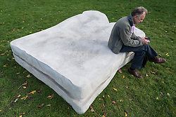 """© Licensed to London News Pictures. 07/10/2020. LONDON, UK. A man sitting on """"Sandwich"""", 2011-2020, by Sarah Lucas at Frieze Sculpture, an annual exhibition of outdoor works by international artists in Regent's Park.  The works are on display to the public until 18 October.  Photo credit: Stephen Chung/LNP"""