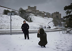 © Licensed to London News Pictures. 07/02/2021. Dover, UK. People take photographs below a snow covered Dover Castle in Kent as parts of the south east of England are hit by the effects of Storm Darcy. Photo credit: Peter Macdiarmid/LNP