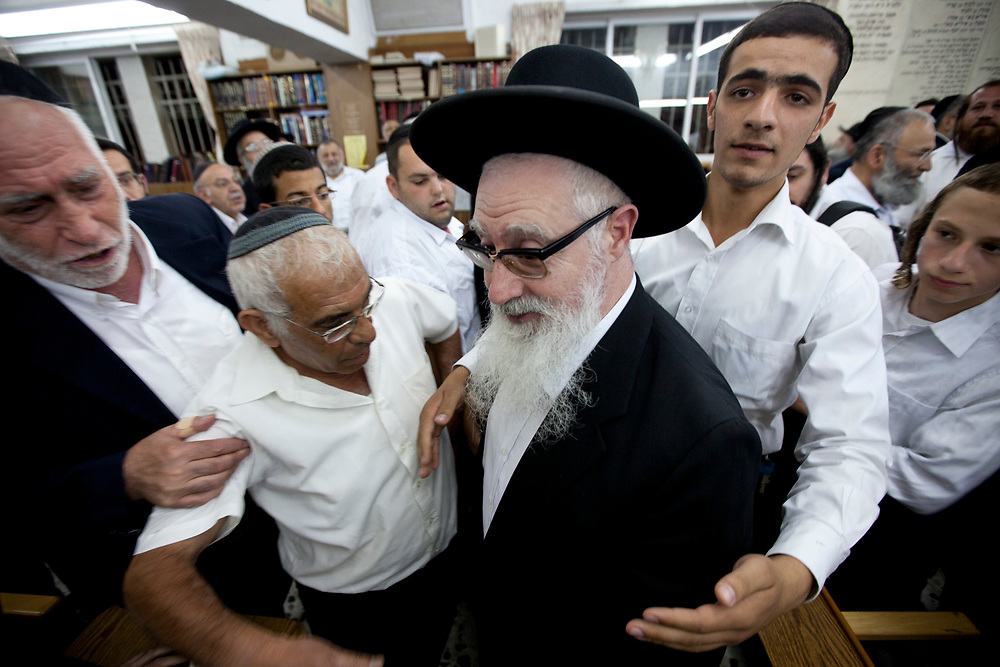 Followers and supporters of Rabbi Ya'akov Yosef (C), son of Rabbi Ovadia Yosef and the one who gave halachic backing to fight against discrimination and segregation in Beit Ya'akov religious school for girls in Emmanuel, surround him during a rally in support of him in Jerusalem on June 23, 2010.