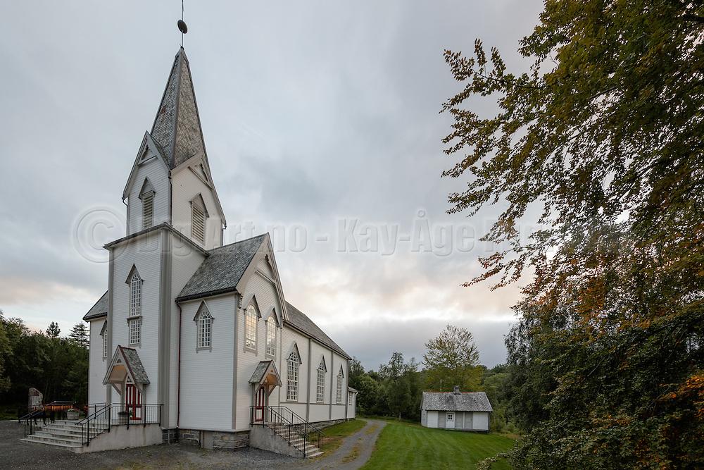 Oversiktsbilde utvendig over Indre Herøy Kirke, samt uthuset (utedoen).