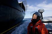 Sea Shepherd crew member Molly Kendall looks up to the main deck of the M/Y Steve Irwin as she rides in the Gemini inflatable fast boat during practice runs in Antarctica's Southern Ocean. (Photo by Adam Lau)