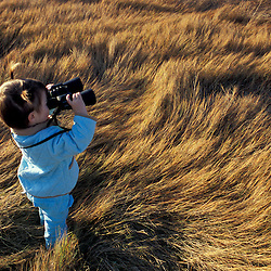 Biddeford, ME. A young girl plays with binoculars on a salt marsh near Biddeford Pool.  TPL project - Anuszewski property.