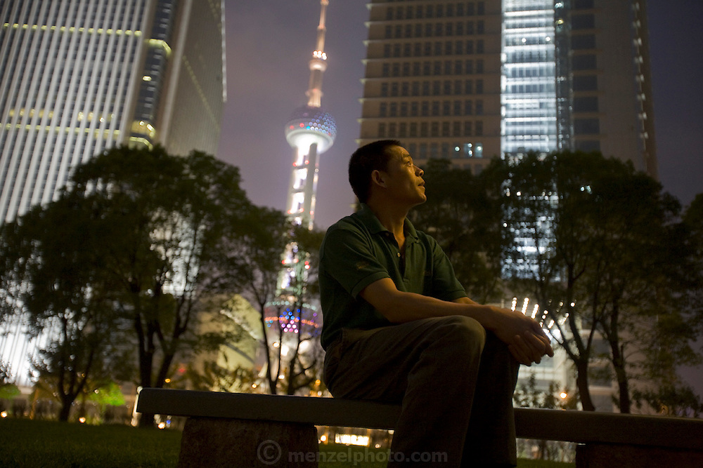Huang Neng, a welder from Henan Province sits in Pudong's Lujiazui Central Green Park in Shanghai, China. (Huang Neng is featured in the book What I Eat: Around the World in 80 Diets). The caloric value of his day's worth of food on a typical day in June was 4300 kcals. He is 36 years of age; 5 feet, 6 inches tall; and 136 pounds. The migrant welder has worked on a dozen trophy skyscrapers on the Huangpu River in Pudong New Area, across the river from old Shanghai. His current project is the Zhongrong Jasper Tower, which will top out at 48 floors, a short-statured building compared to its neighbors. MODEL RELEASED.
