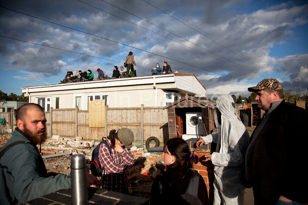 Travellers sit, resigned that they will be removed from their homes in hours. Protesters who barricaded themselves above the entrance to the Dale Farm travellers' site have been removed by police as bailiffs prepare to move in. Essex Police cleared the scaffolding structure so it could be dismantled and machinery driven in by bailiffs to evict the travellers. On Wednesday night Essex Police said that over the course of the day 23 people had been arrested. Clearance of Dale Farm prior to eviction. Riot police and bailiffs were present on 19th October 2011, as a scaffolding gantry was cleared of protesters so the site could be cleared. Dale Farm is part of a Romany Gypsy and Irish Traveller site on Oak Lane in Crays Hill, Essex, United Kingdom. Dale Farm housed over 1,000 people, the largest Traveller concentration in the UK. The whole of the site is owned by residents and is located within the Green Belt. It is in two parts: in one, residents constructed buildings with planning permission to do so; in the other, residents were refused planning permission due to the green belt policy, and built on the site anyway.