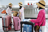 Students from Kyoto, Japan receive their luggage at the baggage claim in Terminal 1 of Lambert-St. Louis International Airport.