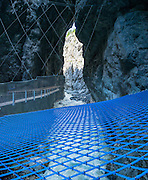You can walk across a blue net suspended over the White Lütschine river gorge in the Gletscherschlucht of Grindelwald, in Switzerland, Europe. The tongue of Lower Grindelwald Glacier last extended through Gletscherschlucht gorge in 1855 and has receded very rapidly, melting back more than 3.75 kilometers as of 2014. Consistent with a pattern global warming, the glacier may entirely disappear by 2100. This image was stitched from multiple overlapping photos. From Gletscherschlucht hotel restaurant in Grindelwald, a wooden walkway leads over raging water, through galleries and rocky tunnels over 1000 meters into the ravine, under 100-meter high cliffs. Visitors can amble on a blue net over the foaming torrent. Walk there in 35 minutes from the center of Grindelwald, or take the bus.
