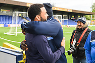 AFC Wimbledon Forward Andy Barcham (17) and Wycombe Wanderers Forward Adebayo Akinfenwa (20) greet each other ahead of the EFL Sky Bet League 1 match between AFC Wimbledon and Wycombe Wanderers at the Cherry Red Records Stadium, Kingston, England on 27 April 2019.