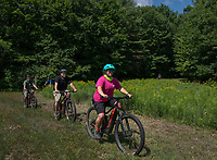 Sara Caveney guides Pat O'Brien, Jeremy Lambert and Charles DeCoff on an EBike tour around Darcy's Garden at Gunstock Tuesday morning.  (Karen Bobotas/for the Laconia Daily Sun)