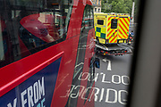 A bus passenger looks towards a London Ambulance being transported on a low-loader lorry, on 30th May 2019, in London, England.