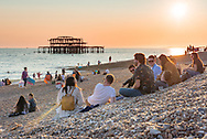 A small group of people meet on the beach at Brighton at sunset