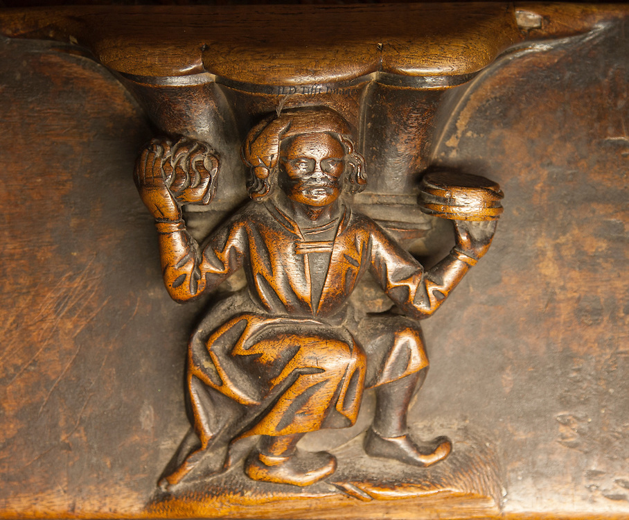 Toledo misericord: man seqted, holding up a loaf (of bread?) in each hand as though offering or serving them.  He wears a tasseled cap and a long coat with sleeves.