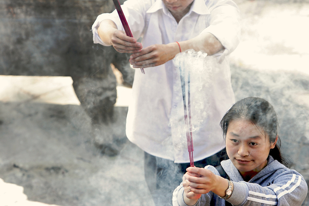 Daoists offer incense at the largest temple in the center of Baiyunguan.Baiyuguan,called White Cloud Temple in English, is over 1,200 years old and stands the south west of Beijing, China.  White Cloud Temple is the largest Daoist structure in Beijing and home of the Dragon Gate sect of Daoism.