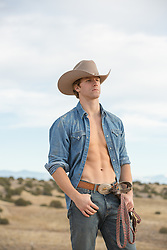 sexy young cowboy with an open shirt outdoors