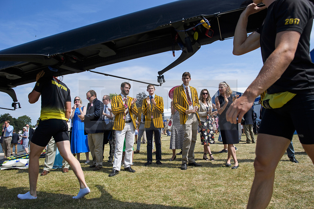 © Licensed to London News Pictures. 04/07/2018. Henley-on-Thames, UK. A group of men in rowing club colours watch as a team takes their boat to the water on day one of the Henley Royal Regatta, set on the River Thames by the town of Henley-on-Thames in England. Established in 1839, the five day international rowing event, raced over a course of 2,112 meters (1 mile 550 yards), is considered an important part of the English social season. Photo credit: Ben Cawthra/LNP