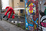 Man dressed as Santa Claus jumps over a fence near to Brick Lane, London, UK. As Christmas comes to a close he is seen running away as if guilty of some kind of offense.