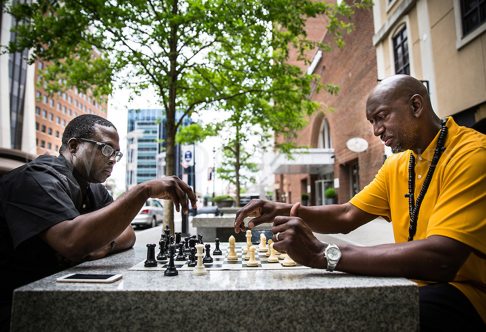 Dante Evans of Johnson County, pictured left, begins his counter attack in anticipation of Abdul Birmingham's, Raleigh, movement of his bishop in their well played chess game along Fayetteville Street on April 20. Evans and Birmingham meet almost every day to compete against one another and others who gather at the tables to play a friendly game of chess.