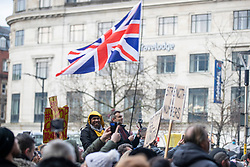 © Licensed to London News Pictures. 06/12/2020. Manchester, UK. People hold signs under a Union Jack flag in Piccadilly Gardens during a Rise Up protest in Manchester. Photo credit: Kerry Elsworth/LNP