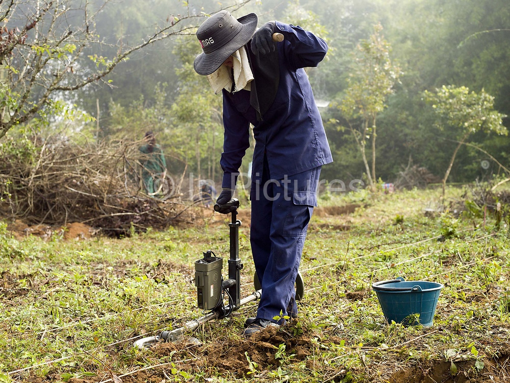 Laos is the most bombed country, per capita, in the world with more than 270 million cluster bomb submunitions dropped on it during the Vietnam War from 1963 to 1974. The Mines Advisory Group (MAG) are a humanitarian organisation clearing the remnants of conflict worldwide and have been working in Lao PDR since 1994. UXO clearance team 6 (UCT6) is an all-female team, one of MAG's seven UXO clearance teams in Xieng Khouang Province, one of the most heavily bombed provinces in Lao PDR.  Pheng (38), MAG Technician, UXO clearance team 6 (UCT6) searchs for UXO with a metal detector on the clearance site in Ban Namoune.