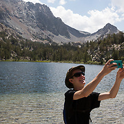 The Eastern Sierras near Mammoth and June Lakes is a outdoor playground that offers incredible fishing, hiking, paddle boarding and scenic wonders. A hiker takes a selfie.