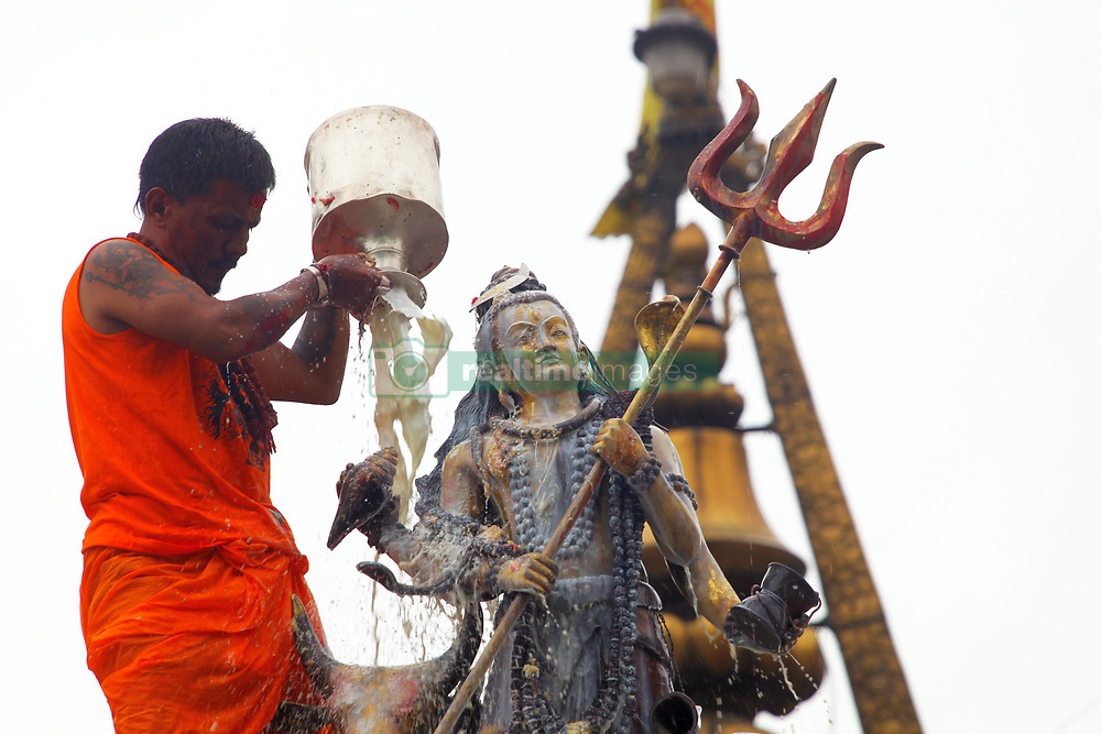 July 30, 2017 - Kathmandu, Nepal - A Hindu priest pours milk to the idol of Lord Shiva while offering prayers at the Shiva temple. The Shrawan month is considered by Hindus auspicious for offering prayers to Lord Shiva, the god of destruction and creation, for happiness and prosperity. (Credit Image: © Sunil Sharma via ZUMA Wire)