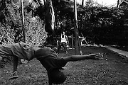 """MERU, KENYA - AUGUST 22, 2011: Kamau """"Kelly"""" Ng'ang'a, 22, trains with handmade cement weights in the yard of his childhood home while niece Njeri, 4, and nephew Edwin, 8, practice somersaults. Ng'ang'a built his home training facility by hand in 2010, allowing him to continue training as a boxer while visiting family in Kenya's rural Eastern Province. """"I'm young, but with boxing I'm going to succeed in life,"""" Ng'ang'a said. """"I need to struggle now when I'm strong so that later on, I'll have time to relax and have a family.""""<br /> <br /> Within Kenya's progressive youth culture is the Kibera Olympic Boxing Club, a group of low-income adolescents from the slum whose leader uses boxing as a way to engage with idle youth. The group's ethnic diversity is remarkable given Kenya's 2008 post-election violence in which people from several tribes were forced violently out of slums. Together, these boxers represent a nascent trend of cross-tribe brotherhood in a healing nation."""