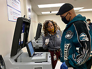 Election worker Hazel Rountree explains how to place a ballot in the optical scanner on the first day of early voting in Ohio.