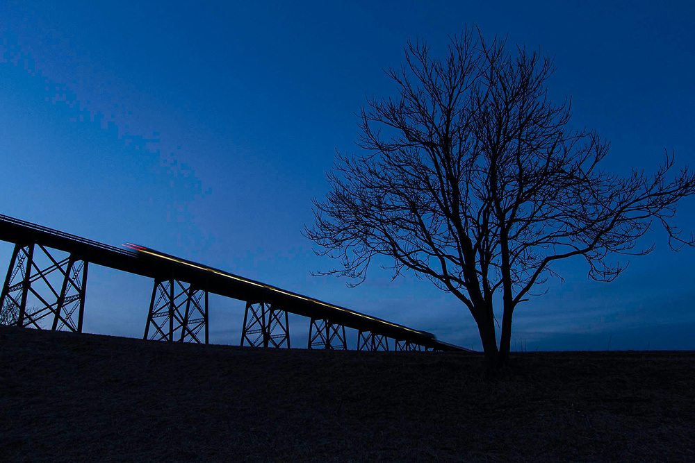 The sun has gone down, stars are just starting to appear overhead, and commuters are still making their way home from Hoboken to close a long day. Metro North train #57 crosses Moodna Viaduct in Salisbury Mills, NY on its journey to Port Jervis. Shot at 6:00pm on Feb. 22, 2012.