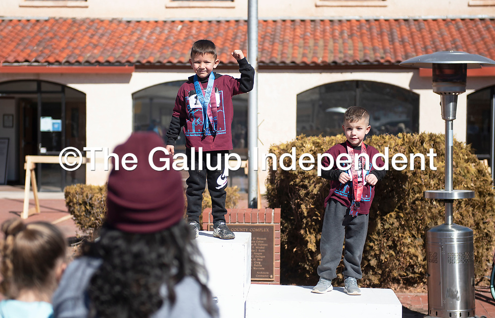 Johnny Melonas, center, and Maverik Garcia receive medals for placing first and second in the Quad Kids 3-4 year old boys age group Saturday afternoon in Grants. The Quad Kids complete an obstacle course in the downtown area of Grants near the finish line of the Mt. Taylor Quadrathlon.