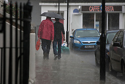 © licensed to London News Pictures. London, UK 08/07/2012. People walking under the rain today. Weather forecasts predict more rain to come this week. Photo credit: Tolga Akmen/LNP