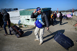 © Licensed to London News Pictures. 25/10/2016. Calais, France.  A migrant man carry all of his belongings leaves the migrant and refugee camp in Calais, known as the 'Jungle'. French authorities have moved thousands of refugees and migrants living at the makeshift living area on the French coast, with some still refusing to leave. . Photo credit: Ben Cawthra/LNP