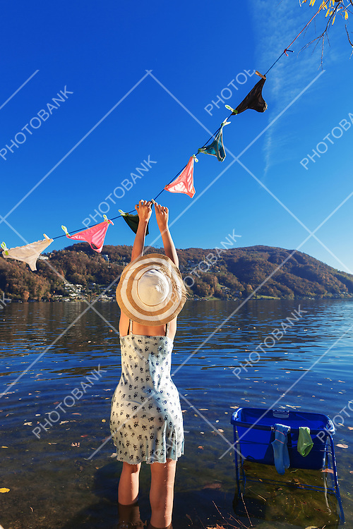 Girl hanging clothes by the lake