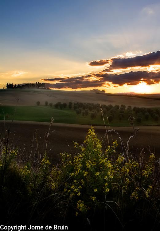 Sunset over Tuscan farmland in autumn.