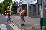 Attractive Polish teenage girls carrying bag of charcoal and grill across street. Tomaszow Mazowiecki Central Poland