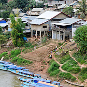 Numerous boats are moored along the town waterfront in Nong Khiaw in northern Laos. This shot, taken from the high bridge spanning the river, provides an elevated view of the waterfront.