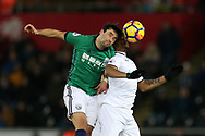 Claudio Yacob of West Bromwich Albion jumps for a header with Jordan Ayew of Swansea city (r). Premier league match, Swansea city v West Bromwich Albion at the Liberty Stadium in Swansea, South Wales on Saturday 9th December 2017.<br /> pic by  Andrew Orchard, Andrew Orchard sports photography.
