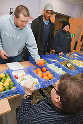 Client buying fresh vegetables form a stall run by people with learning disabilities at a resource for people with physical and sensory impairment.