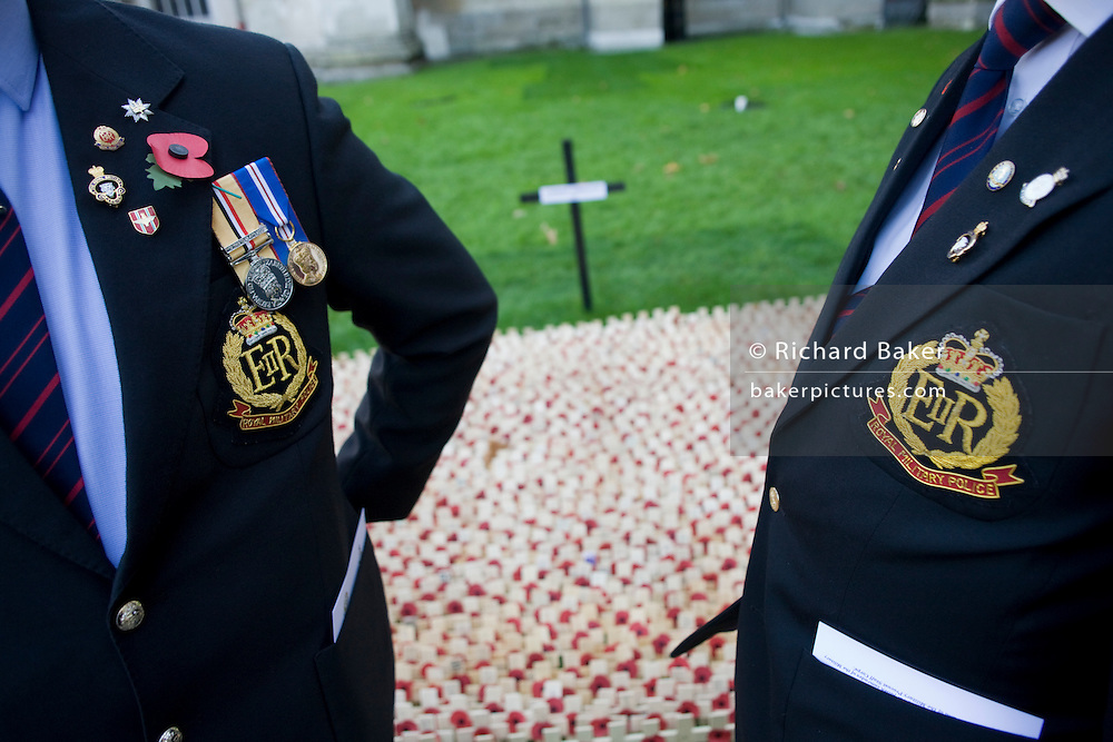 Two serving soldiers in civilian suits but wearing the insignia and badges of the Royal Military Police (RMP), talk quietly together while poignantly paying their respects to the hundreds of markers that symbolise war dead. Crosses and poppies mark anonymous fallen British soldiers and other servicemen and women, all killed during recent conflicts. Dedications from loved-ones or simply well-wishers are written on the wooden crosses on the weekend that Britain commemorates those killed on active service in trouble spots and war locations around the world, the markers a laid on the grass of Westminster Abbey's lawns on Parliament Square, opposite the Houses of Parliament. Armistice weekend is largely held on the closest Sunday to the 11th hour of the 11th Day of the 11th Month, when hostilities famously ended in on 11th November 1918...