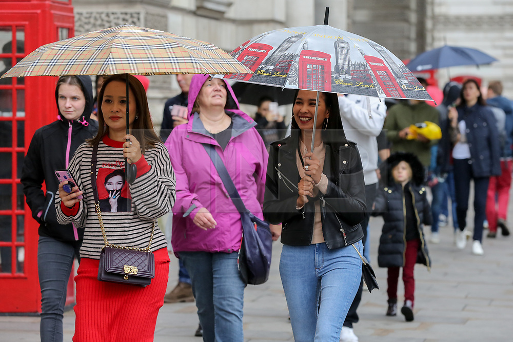 "© Licensed to London News Pictures. 29/09/2019. London, UK. Tourists shelter from rain underneath umbrellas in Westminster, London. According to the Met Office, UK  is braced for one of Europe's strongest-ever hurricanes, ""Hurricane Lorenzo"" which will bring 80mph gales, 16ft waves and snow next week. Photo credit: Dinendra Haria/LNP"