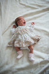 New born baby girl crying on bed, Munich, Bavaria, Germany