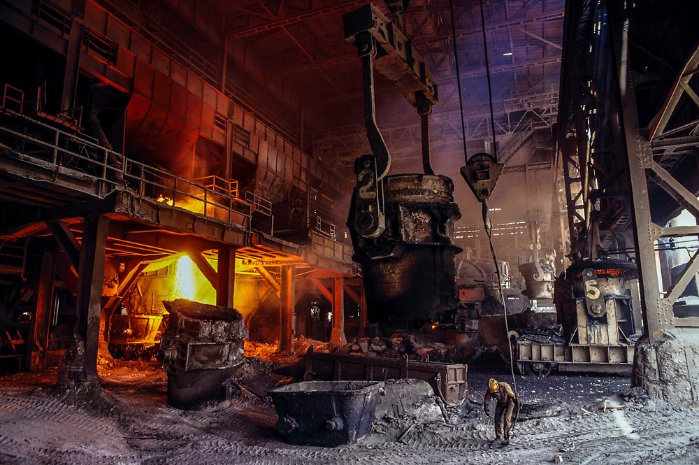 A worker stands near a molten metal ladle in a steel foundry in Boyaca. ca. 2003