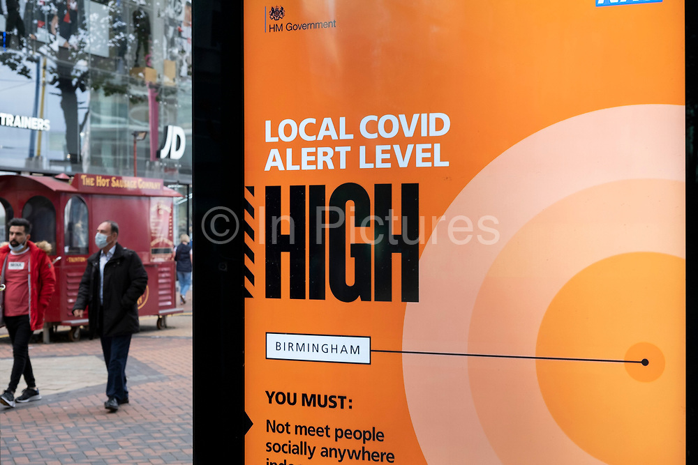 With new local coronavirus lockdown measures now in place and Birmingham currently set at 'Tier 2', people wearing face masks pass a Public Health England / NHS digital information poster advising that the local lockdown level is 'High' in the city centre on 14th October 2020 in Birmingham, United Kingdom. This is the first day of the new three tier system in the UK which has levels: 'medium', which includes the rule of six, 'high', which will cover most areas under current restrictions; and 'very high' for those areas with particularly high case numbers. Meanwhile there have been calls by politicians for a 'circuit breaker' complete lockdown to be announced to help the growing spread of the Covid-19 virus.