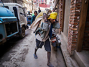 05 MARCH 2017 - KATHMANDU, NEPAL: A porter carries a load of sand to make cement into a site for reconstruction from the 2015 earthquake. Much of Kathmandu is now a construction site because of rebuilding  two years after the earthquake of 25 April 2015 that devastated Nepal. In some villages in the Kathmandu valley workers are working by hand to remove ruble and dig out destroyed buildings. About 9,000 people were killed and another 22,000 injured by the earthquake. The epicenter of the earthquake was east of the Gorka district.     PHOTO BY JACK KURTZ