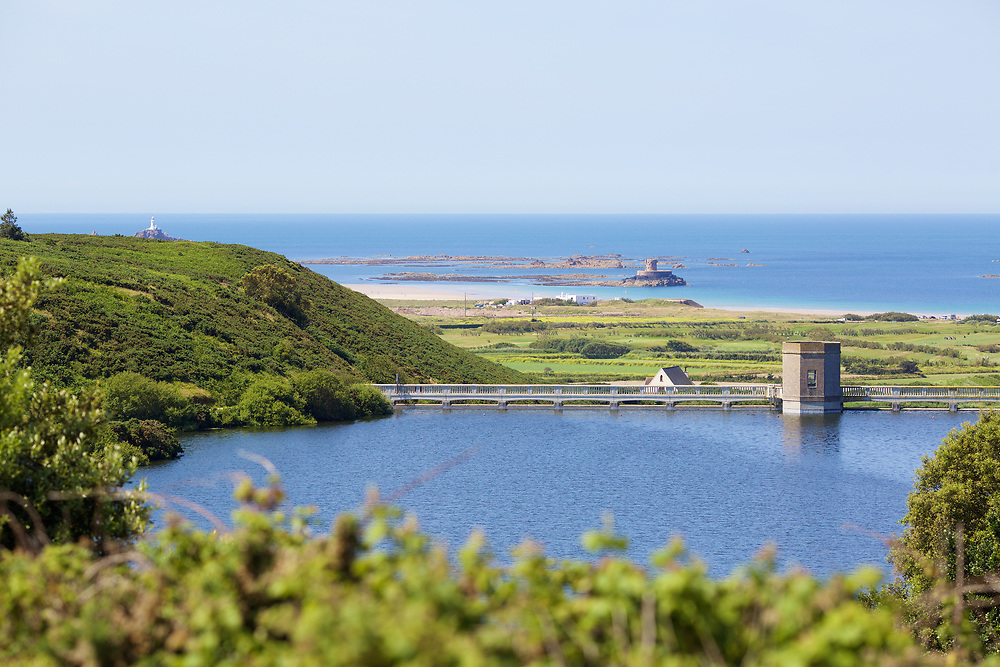 Val de la Mar Reservoir with the view of La Rocco Tower, St Ouen's Bay and Corbiere lighthouse in the distance on a summer day in Jersey